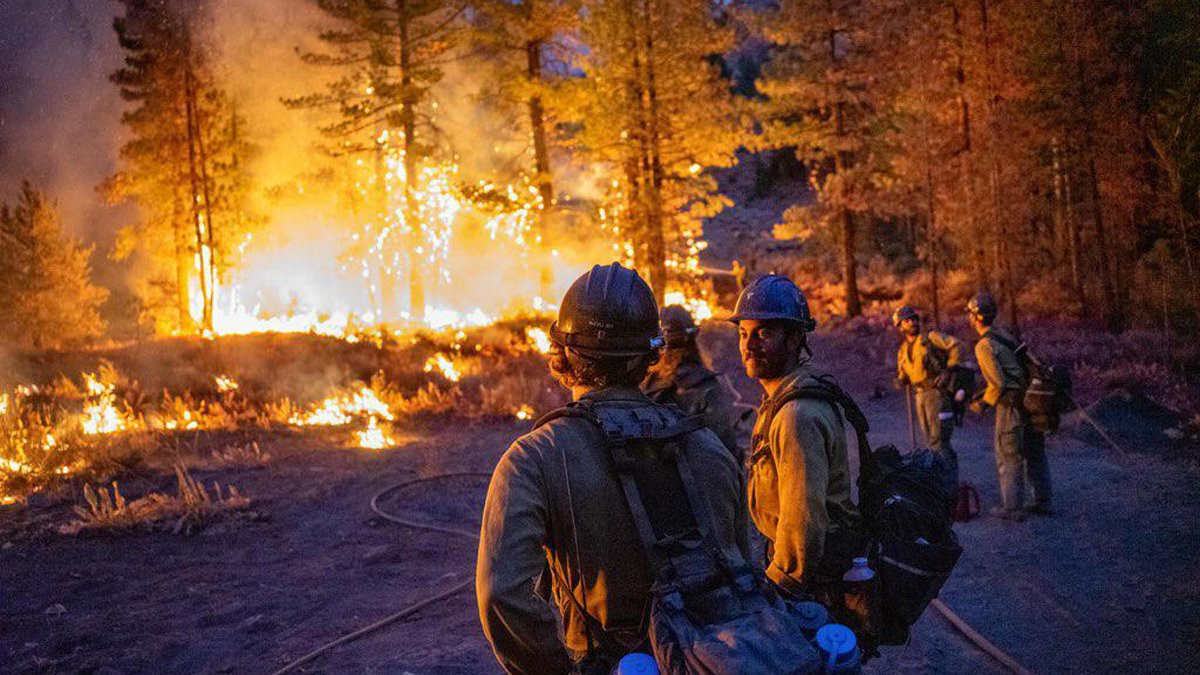 The Ruby Mountain interagency hotshot crew monitors the fireline under the glow of the Dixie...