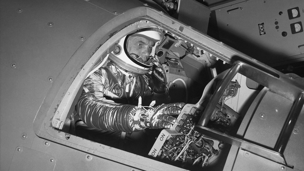FILE - In this Jan. 11, 1961 file photo, then-Marine Lt. Col. John Glenn reaches for controls...